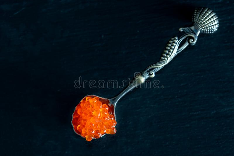 Red caviar in silver spoon on black background royalty free stock image