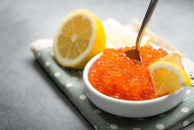 Red caviar with slice lemon. In a white bowl on a table. luxury seafood snack stock photography