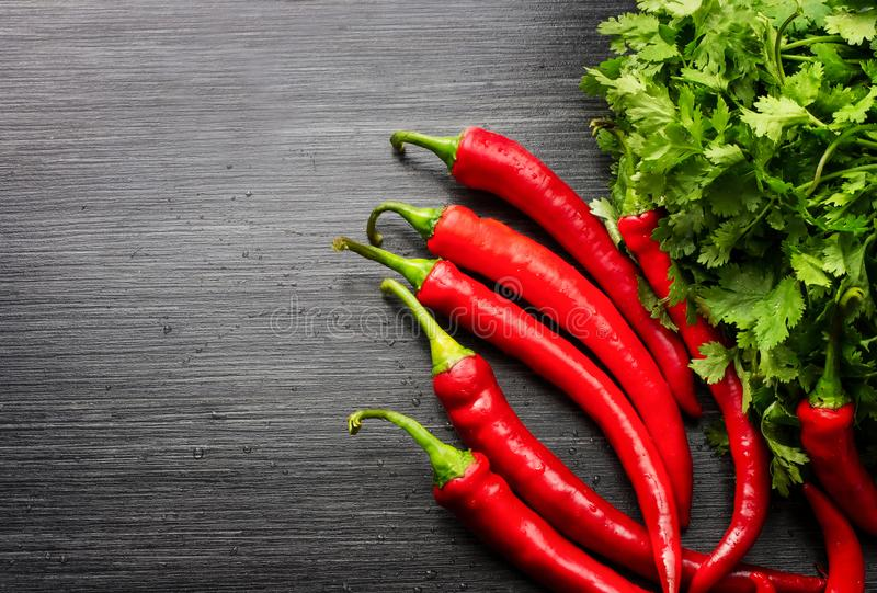 Red cayenne peppers Capsicum annuum and verdure on wooden table. Top view. royalty free stock images