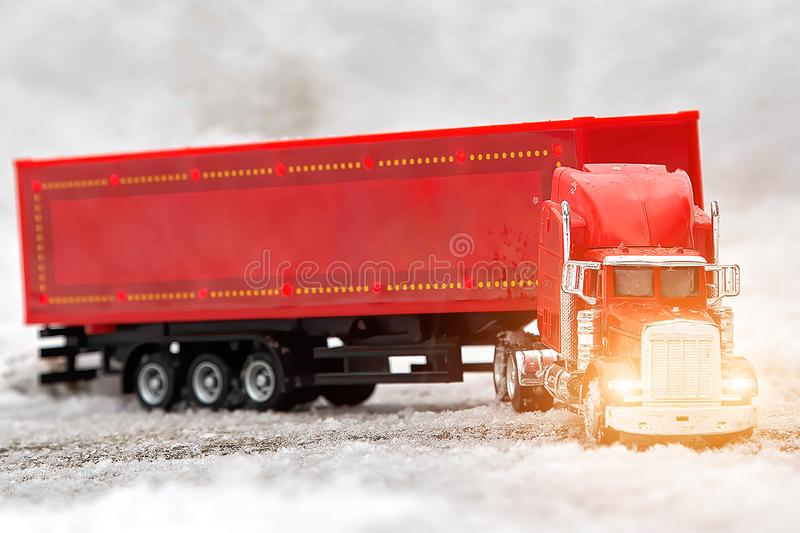 A red celebratory toy truck with a trailer shines headlights ahead. The tractor rides in the snow. Christmas holidays are coming. Front view royalty free stock image