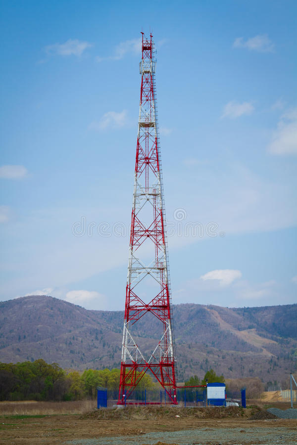 Red cell tower. Construction of a cell tower in the forest stock photography