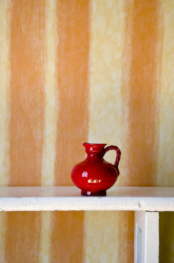 Red ceramic jug on white wooden shelf stock photo