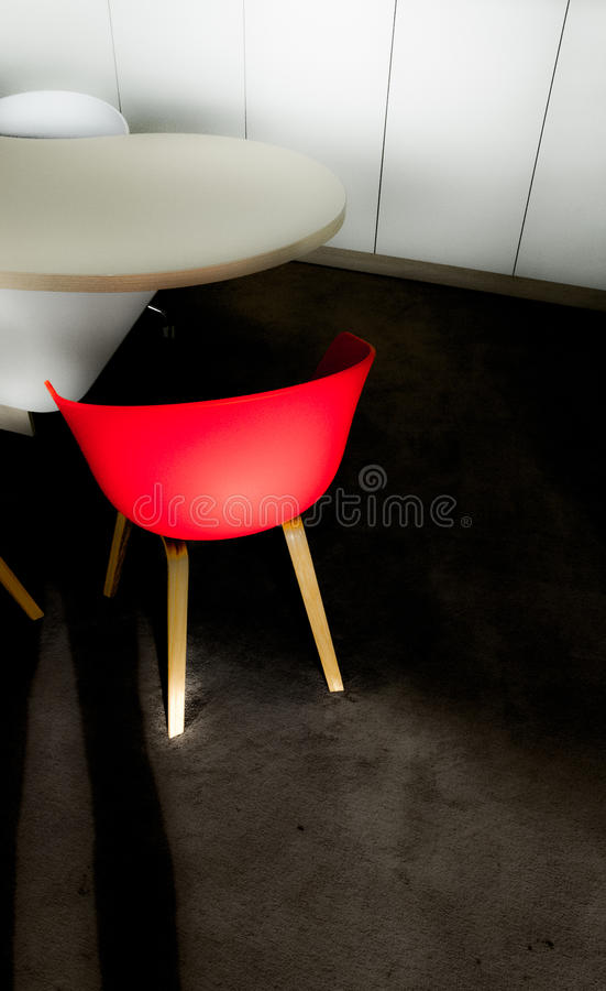 Red chair on a black carpet and a white table stock images