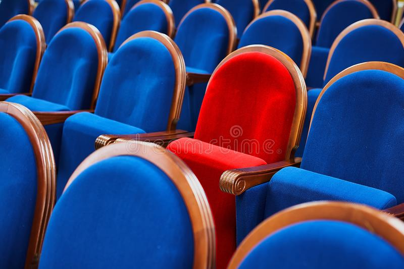 Red chair among the blue seats. Special or VIP seat in the meeting room stock photos