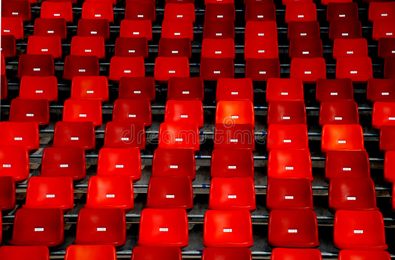 Red chairs. Red seats, plastic chairs in a stadium stock image