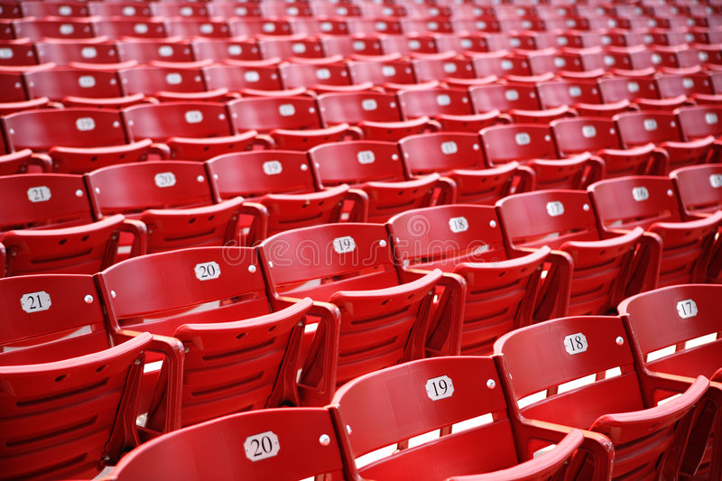 Red chairs. Empty rows of vivid red chairs with numbers stock photo