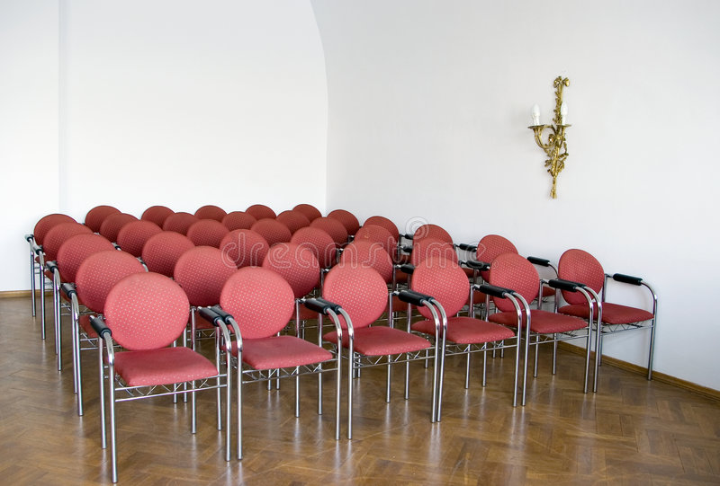 Red chairs in meeting room. Several rows of red chairs in a meeting room or classroom royalty free stock image