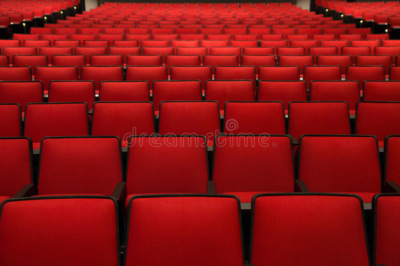 Red Chairs in movie theater. Empty red Chairs in movie theater, view from the side stock photos