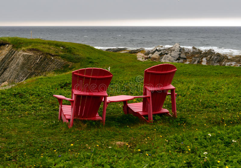 Red chairs. Pair of red chairs near ocean stock photos