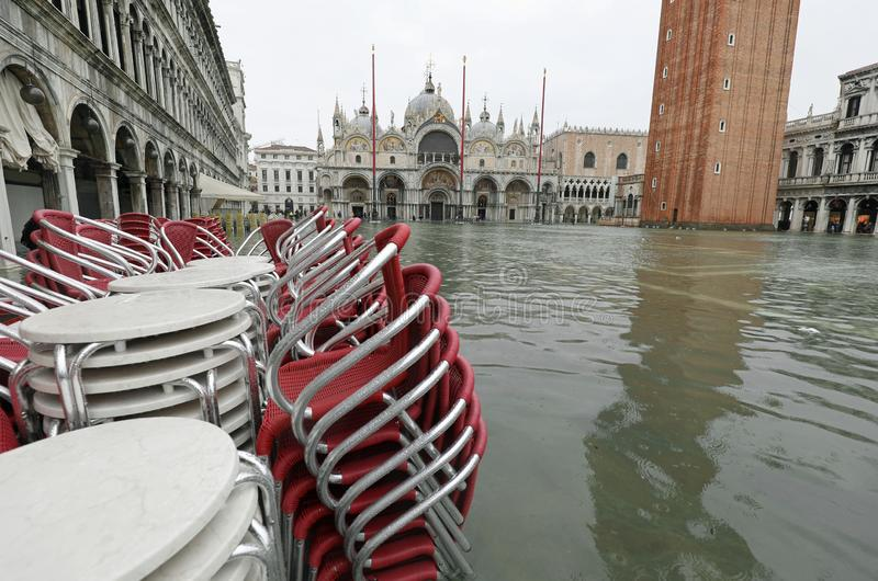 Red chairs of a sidewalk cafe in Saint Mark Square in Venice wit. Red chairs of a sidewalk cafe in Saint Mark Square in Venice Itay with high tide and the royalty free stock photos