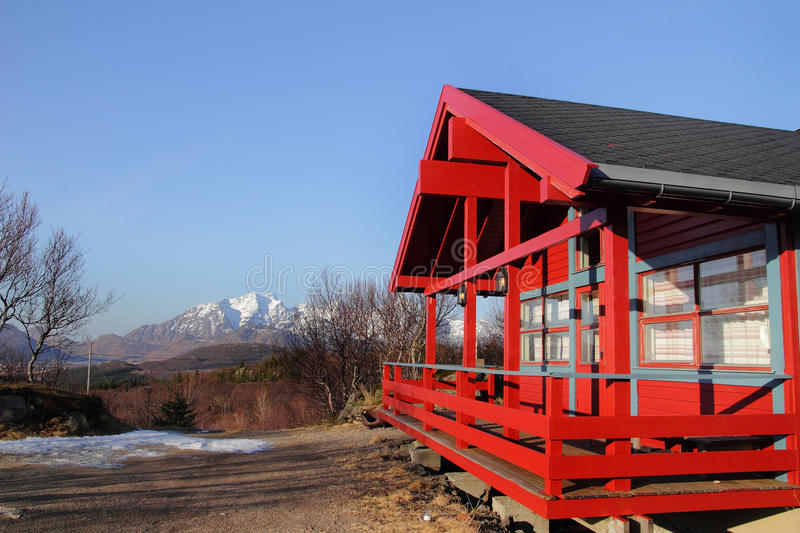 Red chalet and mounts of Lofoten Islands. Wooden cabin on the hills of Hagskaret in Lofoten, the Mount Himmeltinden on the background stock image