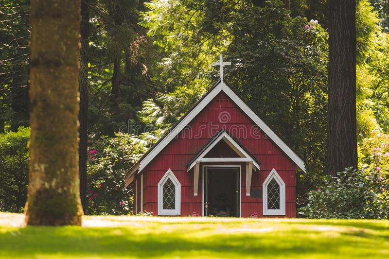 Red Chapel on Grassy Field With Trees stock photography