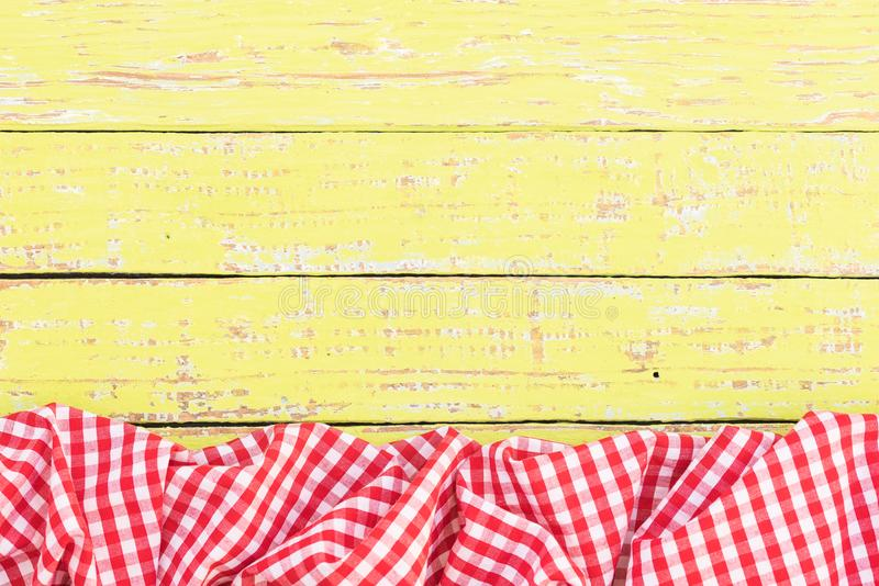 Red checked crinkly tablecloth on rustic wooden table surface, top view. Yellow wooden table background rustic texture, with red checkered tablecloth, high angel royalty free stock photo