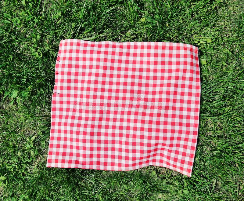 Red checkered cloth on green grass top view. royalty free stock photography