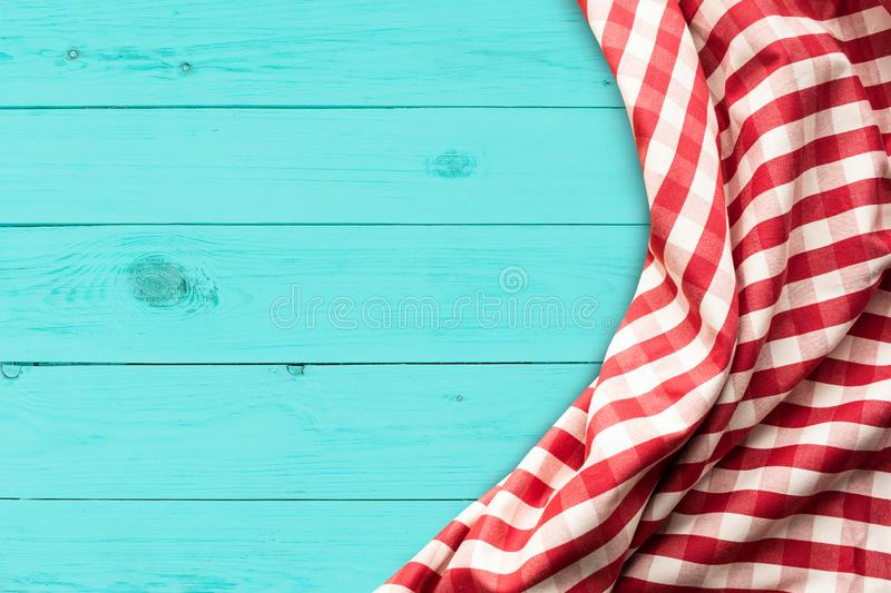 Red checkered fabric on blue wood table background.For decoration key visual l royalty free stock image