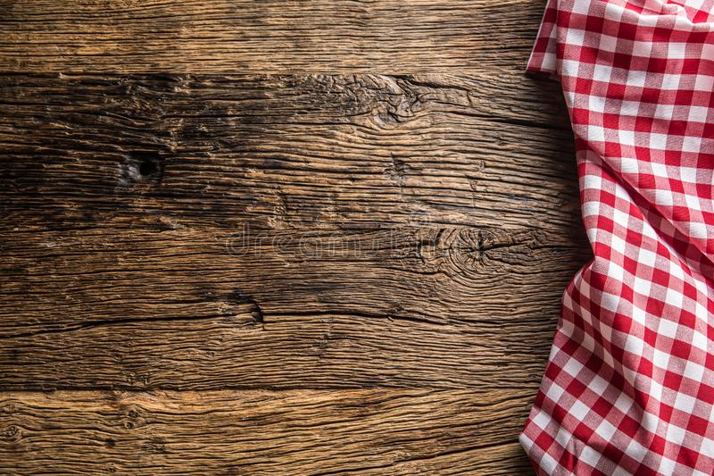 Red checkered kitchen tablecloth on rustic wooden table.  stock images