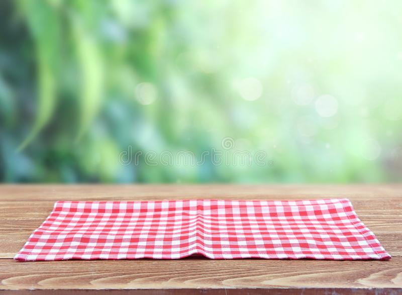 Red checkered picnic cloth on wooden tablue blurred green background. Checkered red picnic folded towel cloth on wooden table blurred green natural background royalty free stock photography