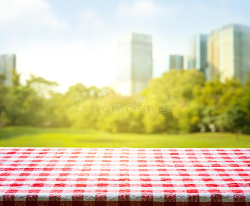 Red checkered tablecloth texture with park in morning royalty free stock image