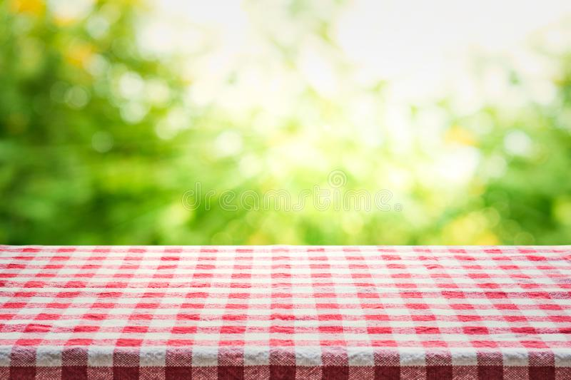 Red checkered tablecloth texture top view with abstract green bokeh stock image