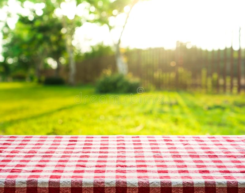 Red checkered tablecloth texture top with view garden, fence. Field background royalty free stock photo