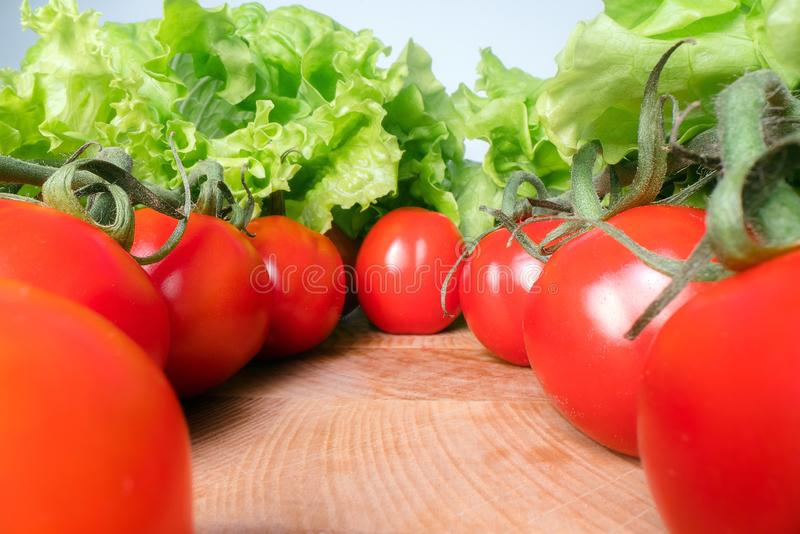 Red cheery tomatoes with lettuce leafs on top of wooden table background. Home grown vegetables, healthy eating lifestyle.  royalty free stock image