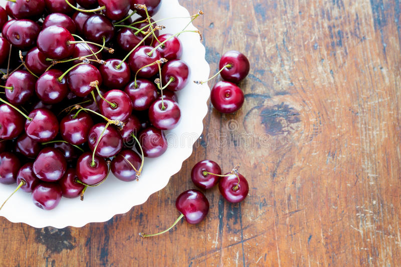 red cherries in bowl on a wooden table stock photo