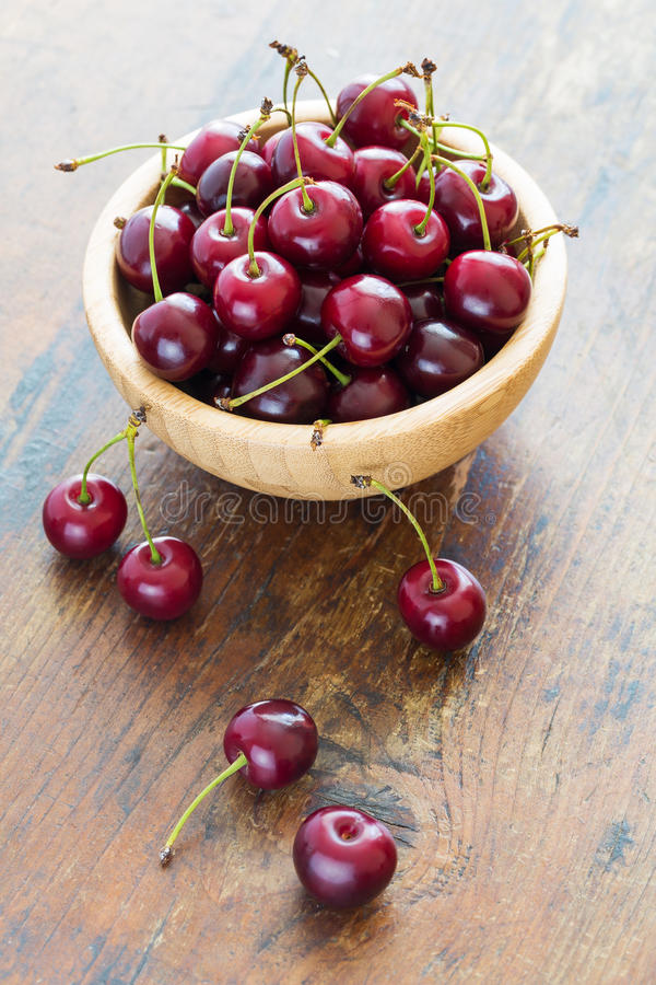 red cherries in bowl on a wooden table stock photography