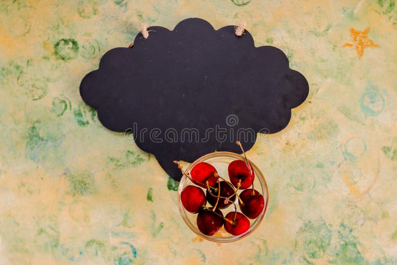 Red cherries in glass on rustic table and empty chalkboard. Overhead view, copy space.ripe sweet cherry and black board stock images