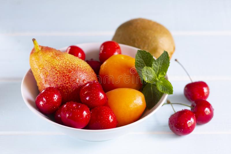 Red cherry, apricots, Forelle pear with fresh mint in a white bowl. Fruit in a bowl. Red cherry, apricots, Forelle pear with fresh mint in a white bowl. Kiwi stock photos