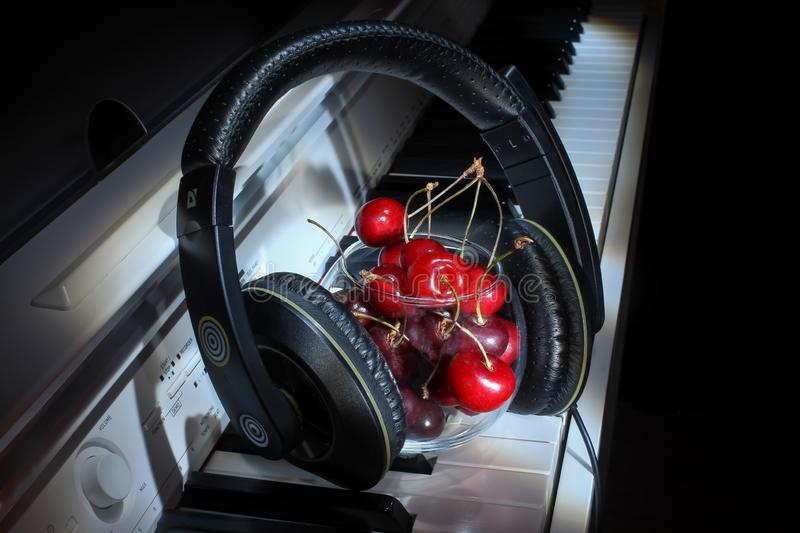 Red cherry berries lie with headphones on the white keys of the classical piano musical instrument, unusual design, beautiful. Beautiful ripe juicy red cherry stock photos