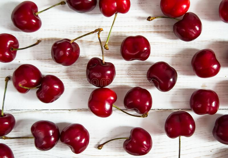 Red Cherry berries scattered on a white wooden table royalty free stock photo