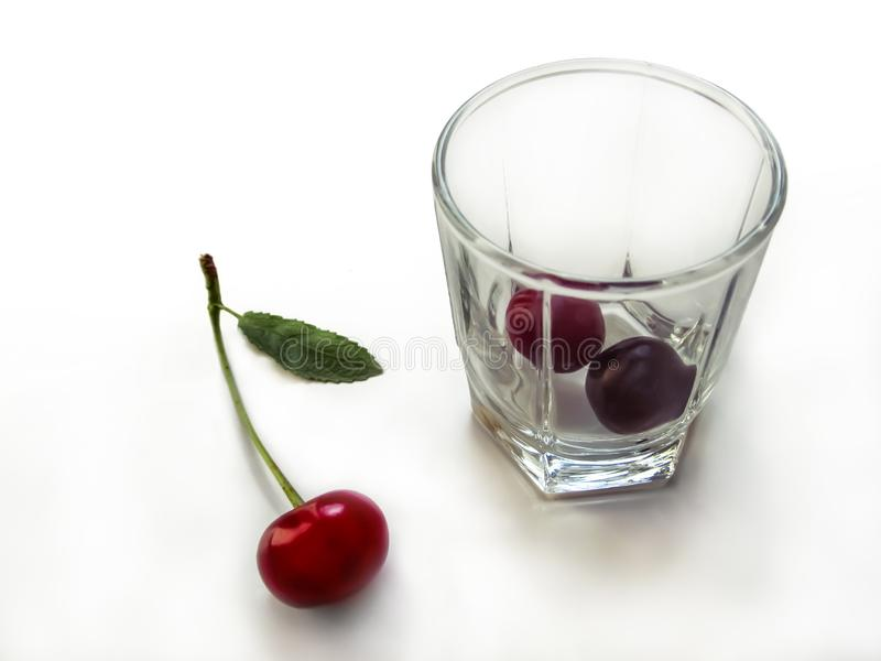 Red cherry fruit with a green stem and leaf lies near a transparent glass with two berries inside. Concept of organic drink and royalty free stock photo