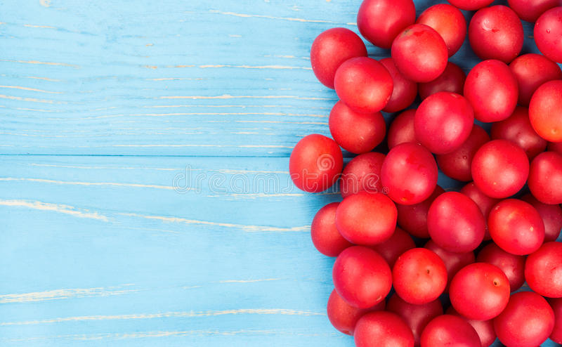 Red cherry plum. Fresh red cherry plum on wooden background empty, top view royalty free stock photos