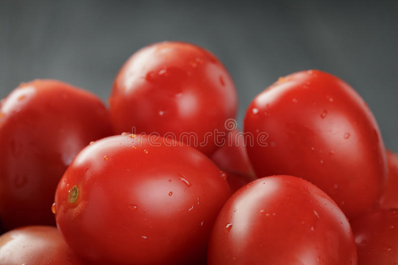 Red cherry or plum tomatoes in bowl. Close up royalty free stock image