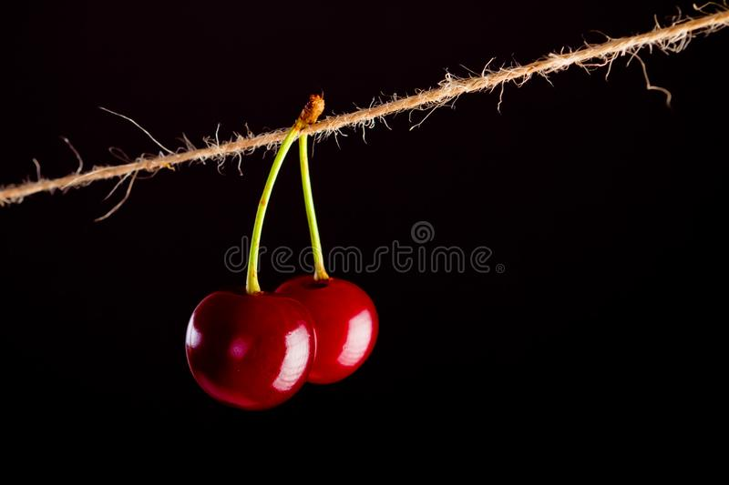 Cherry and rope on black with clamp royalty free stock photography