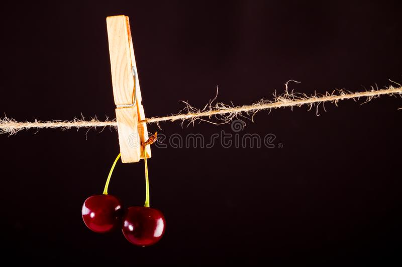 Cherry and rope on black with clamp stock photos