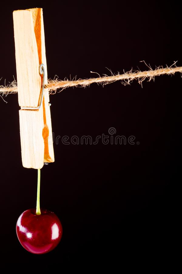 Cherry and rope on black with clamp stock photography