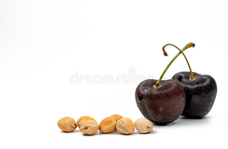 Red cherry with stalk and seed isolated on white background with copy space. Ripe red sweet cherry. Sweet and juicy organic cherry. Fresh fruit for summer stock images
