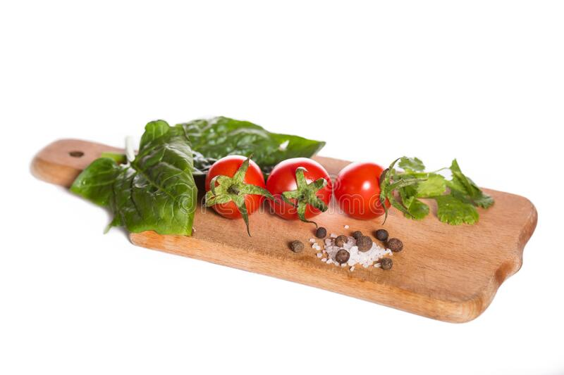 Cherry tomatoes with herbs. Red cherry tomatoes on a kitchen board with herbs isolated on a white royalty free stock photo