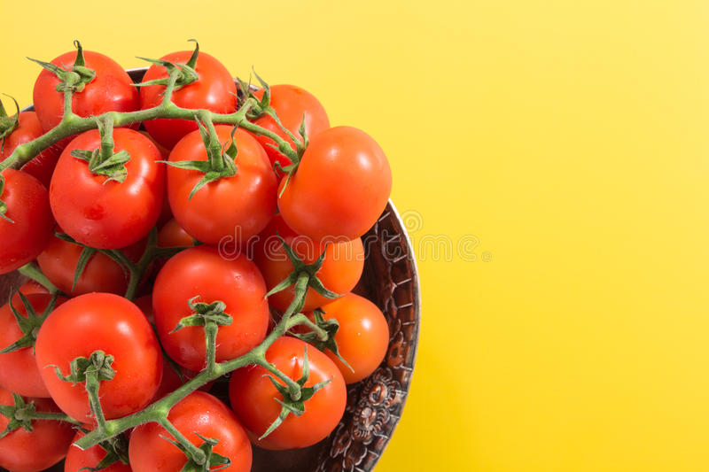 Red cherry tomatoes with stem in antique metallic bowl, on vivid yellow background. With copy-space stock photography