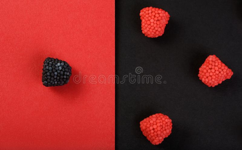 Sweets in the form of fruit berries on red and black. Red chewing candies in form of raspberry on red background and one black candy flavored blackberry on black royalty free stock image