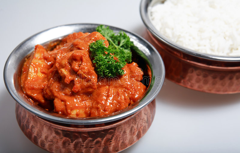 Red chicken curry basmati rice. Serving bowls with a red Thai chicken curry, cooked with coconut milk and mango (topped with a sprig of parsley) and plain white royalty free stock photos