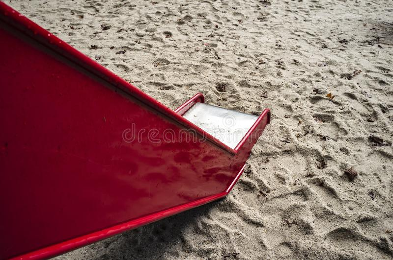 Red, children`s metal slide on the sandy playground stock photo