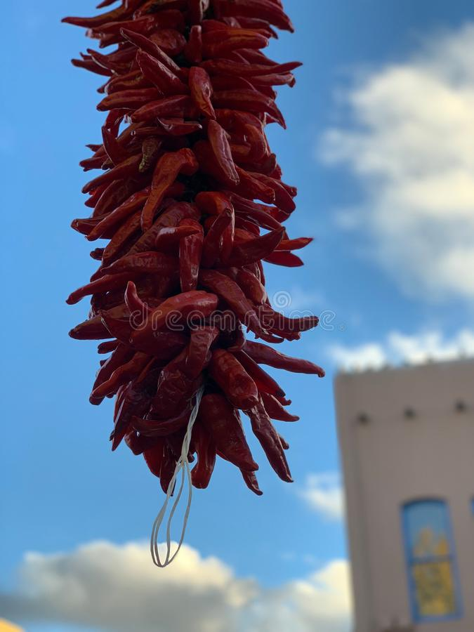 Red chile hanging in Sante Fe New Mexico Downtown. Hanging dry red chile in Santa Fe, New Mexico with blue sky and adobe building in background. Medium shot with stock photography