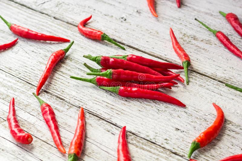 red chili or chilli cayenne pepper on white wooden table stock photography