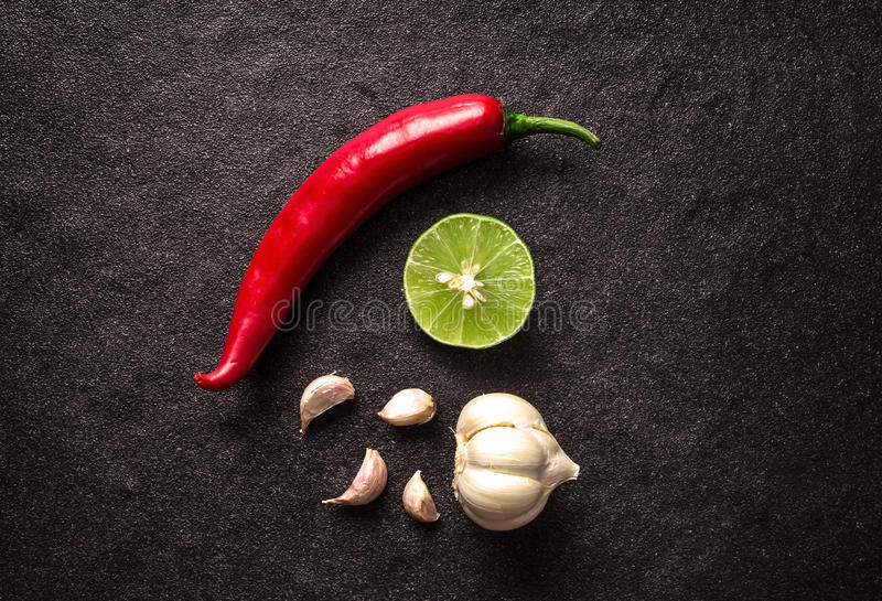 Red chili , garlic and lime lemon arrange on black stone background royalty free stock image