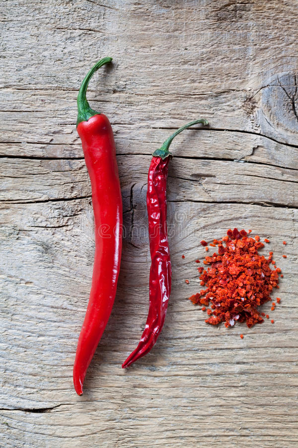 Red Chili Pepper. Fresh, dried and coarsely ground Red Chili Pepper on wooden board royalty free stock photo