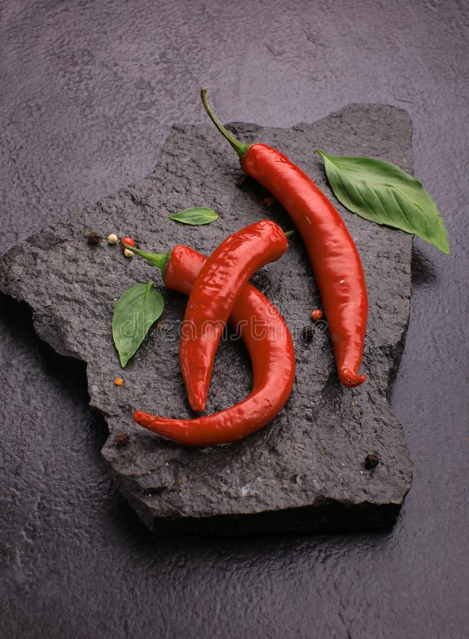 Red chili pepper on black slate. Red chili pepper on a black stone, food, fresh, hot, ingredient, mexican, spice, vegetable, chilli, slate, organic, ripe, spicy stock image