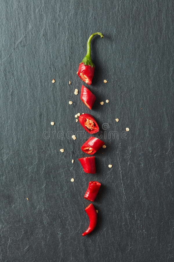 Red chili pepper cut into slices stock images