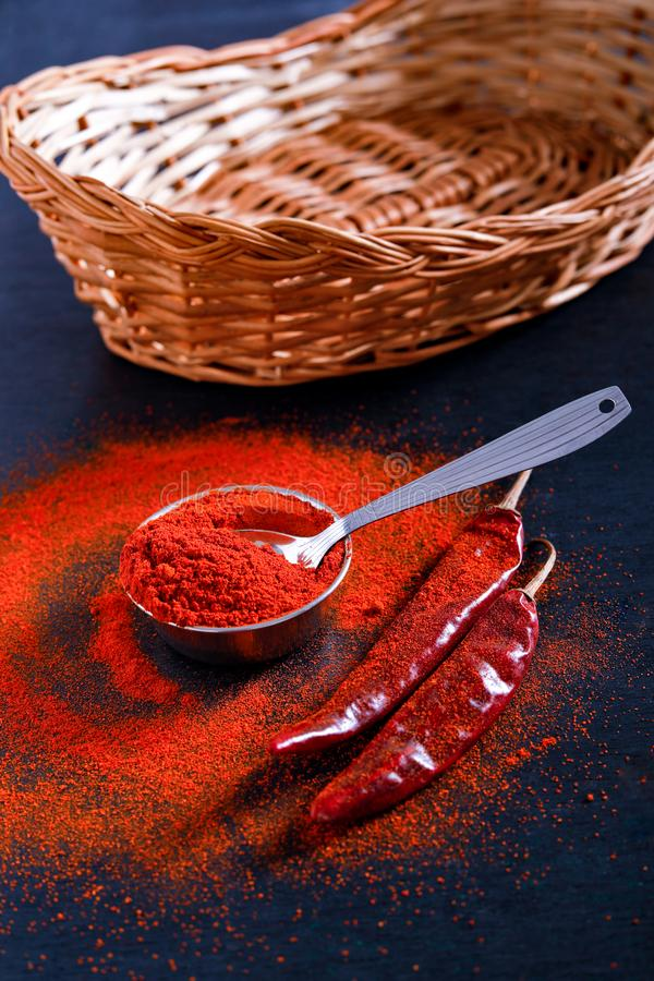 Red Chili pepper flakes and chili powder burst on black background stock image